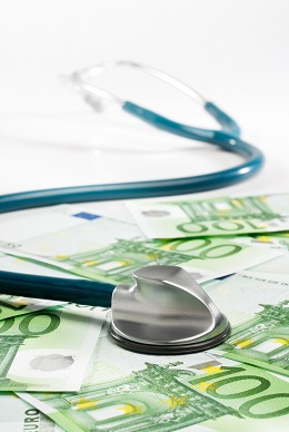Stethoscope on fresh hundred dollar bills as tax penalty for not following healthcare reform.