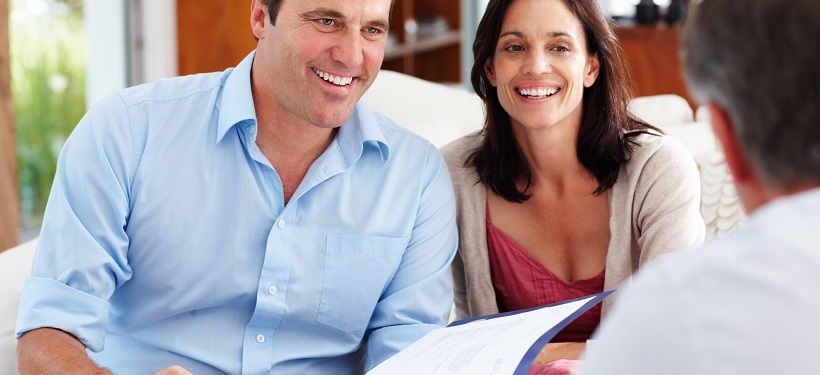 Couple review life insurance with broker